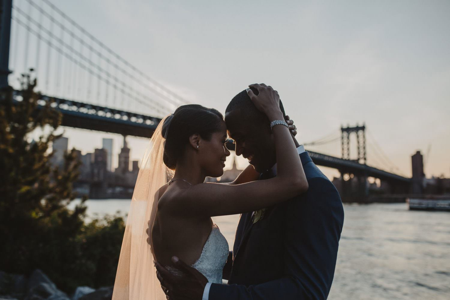 Bride and Groom holding each other in DUMBO near the Manhattan Bride at sunset