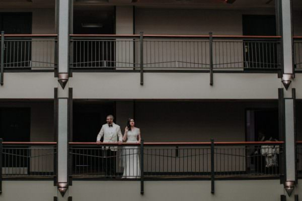 Bride and Groom stand next to each other in the balcony of the Roxy Hotel in New York City