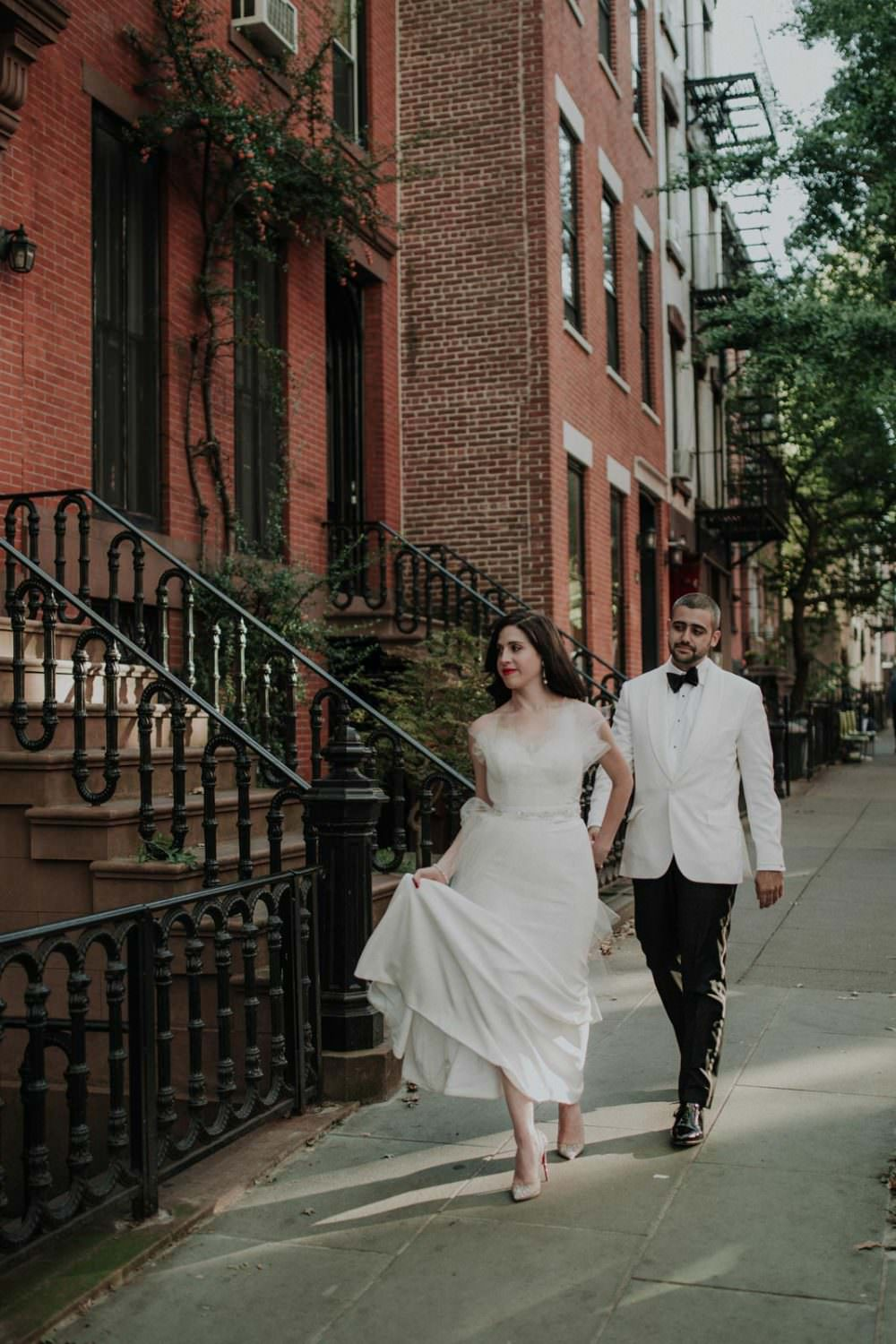 Bride and Groom hold hands while walking on a brooklyn street with brick brownstones behind them