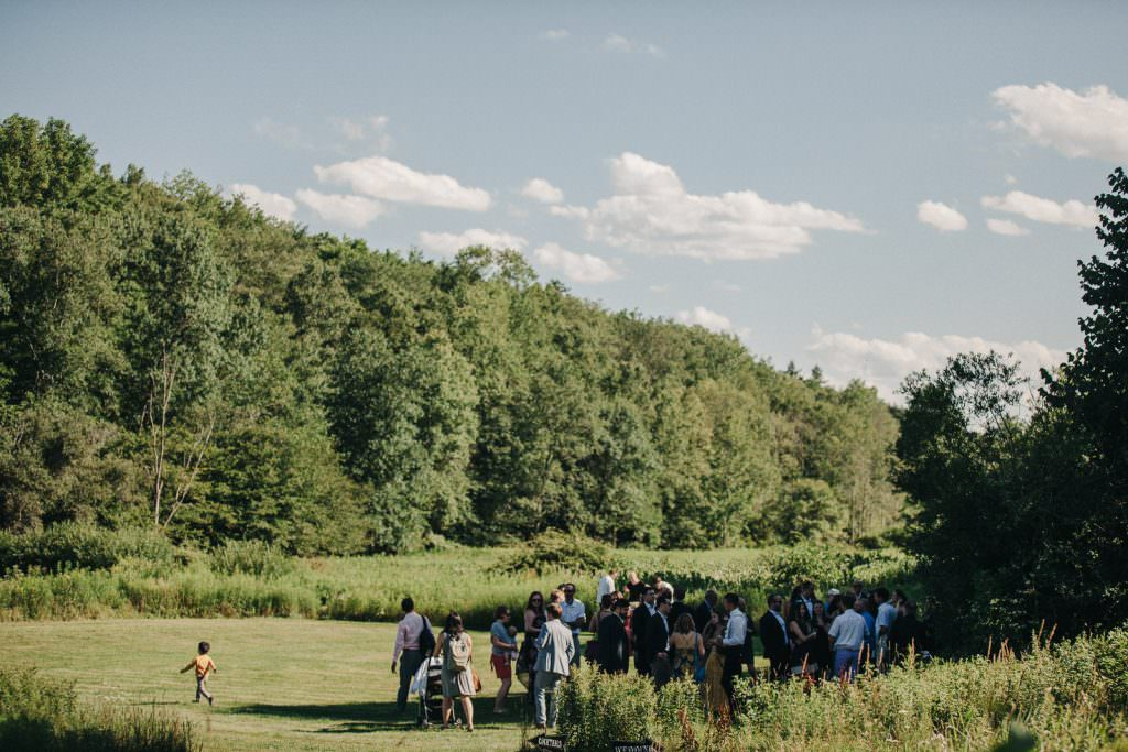 Guests gather on a green open field for a Wedding in the Catskills