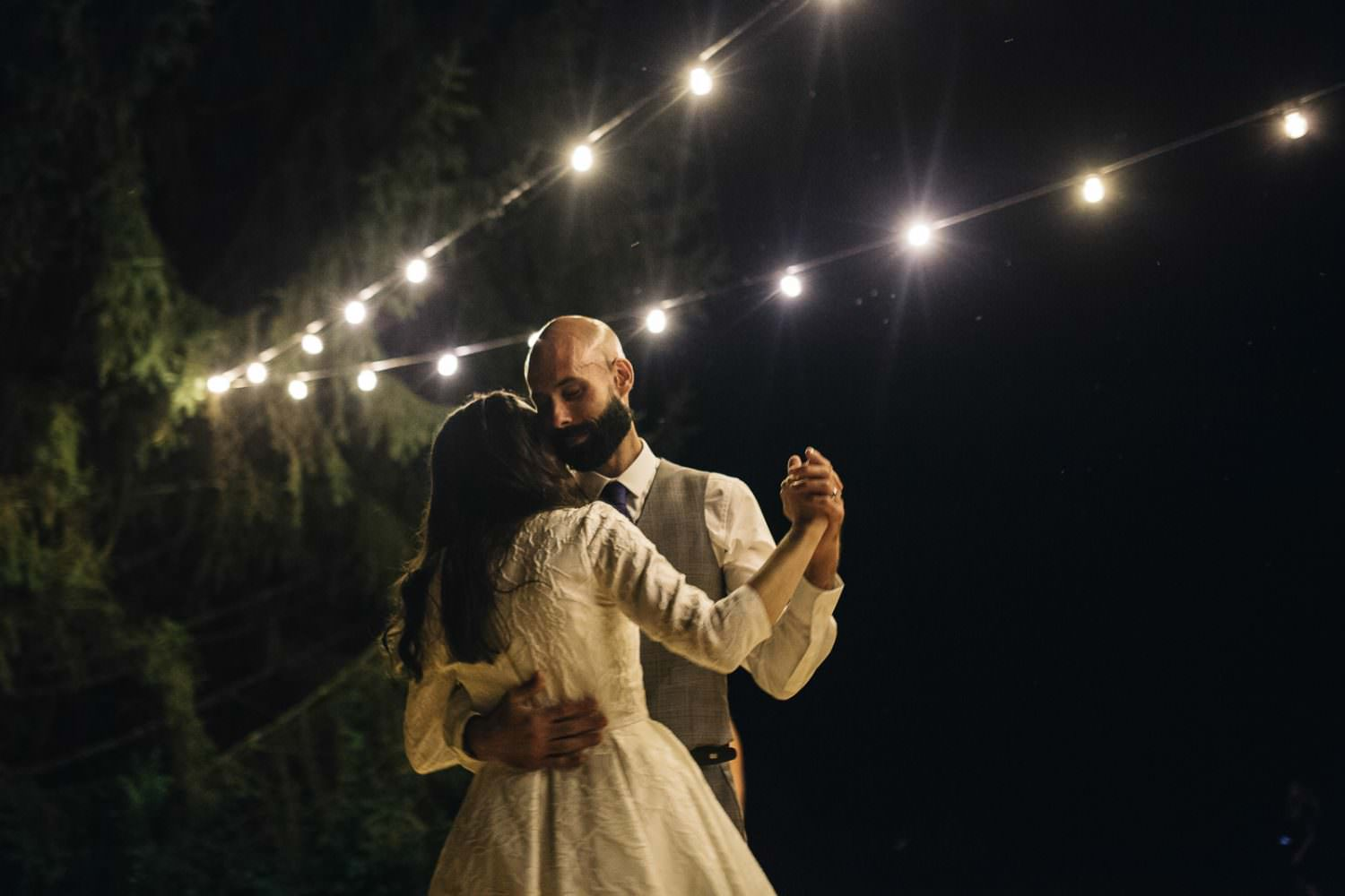 Bride and Groom dance under moonlight and light bulbs on their wedding day