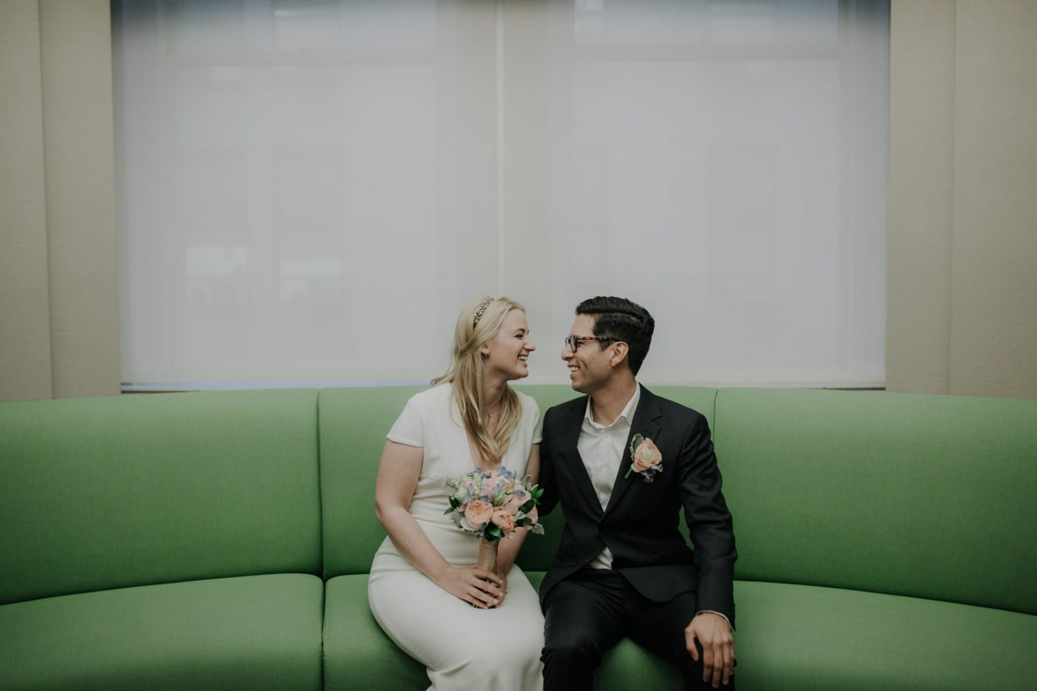 Bride and groom sit on a green couch in city hall NYC