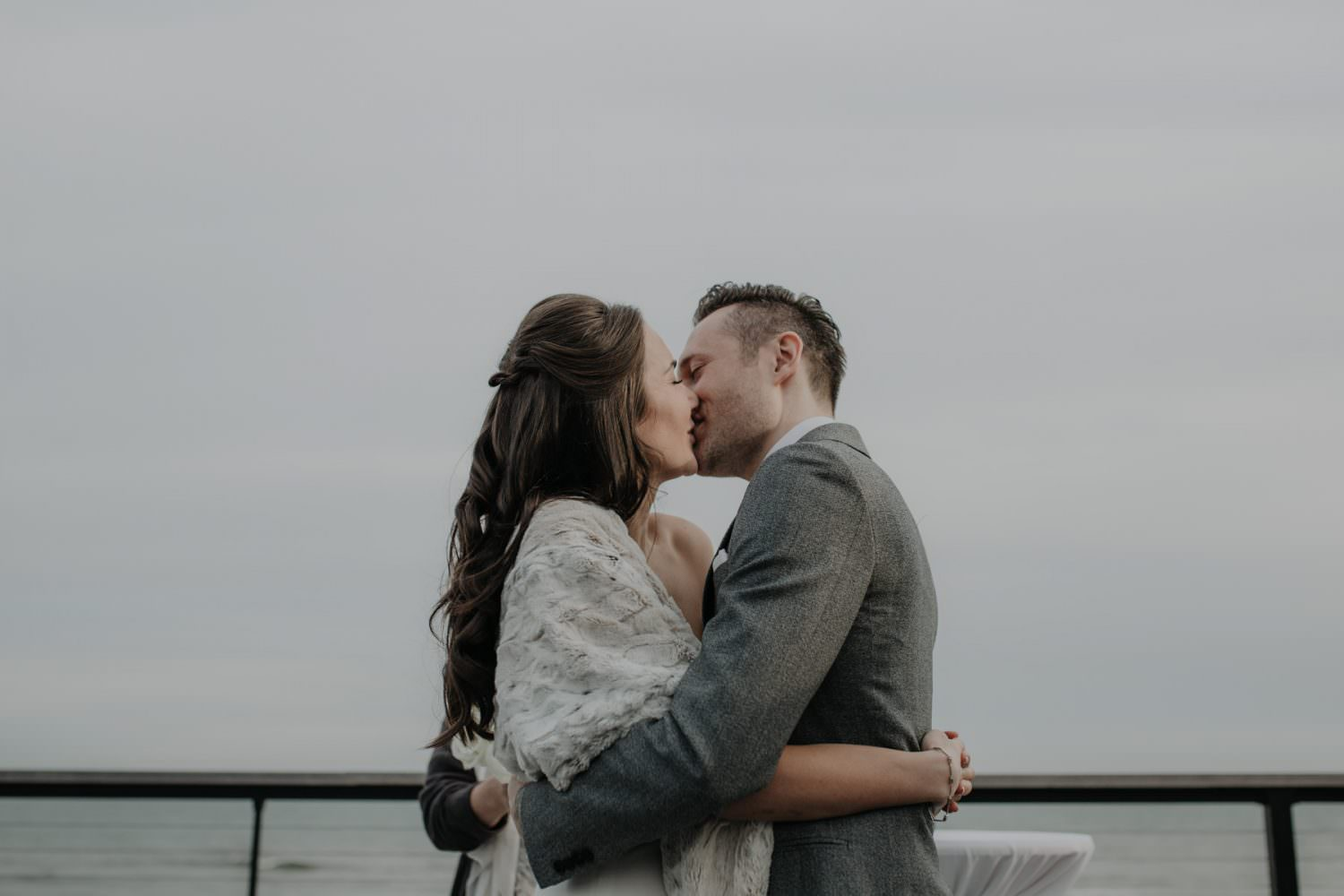 Bride and Groom kiss after their ceremony on the deck of Gurney's Montauk