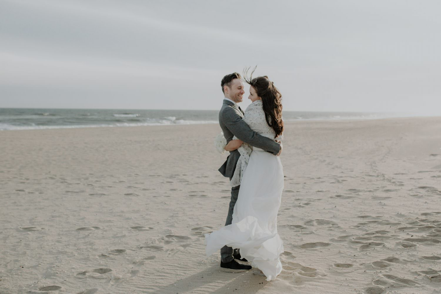 Bride and Groom holding each other on a winter beach scene in Montauk