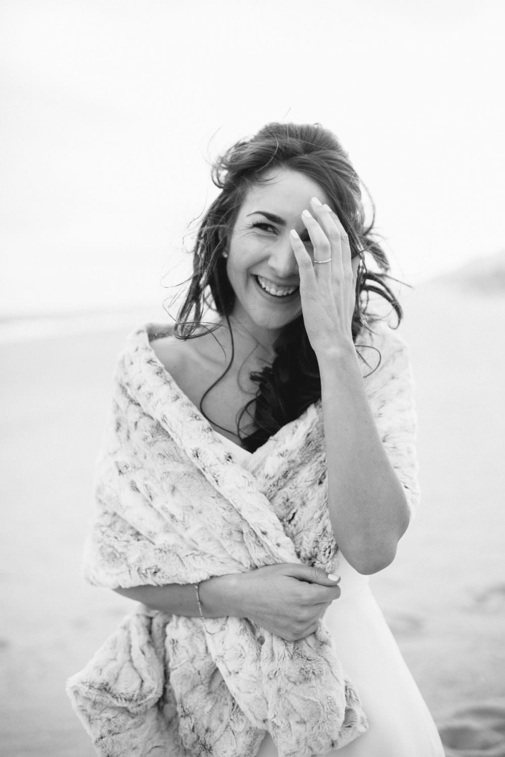 Portrait of Bride holding up her hair on a windy beach