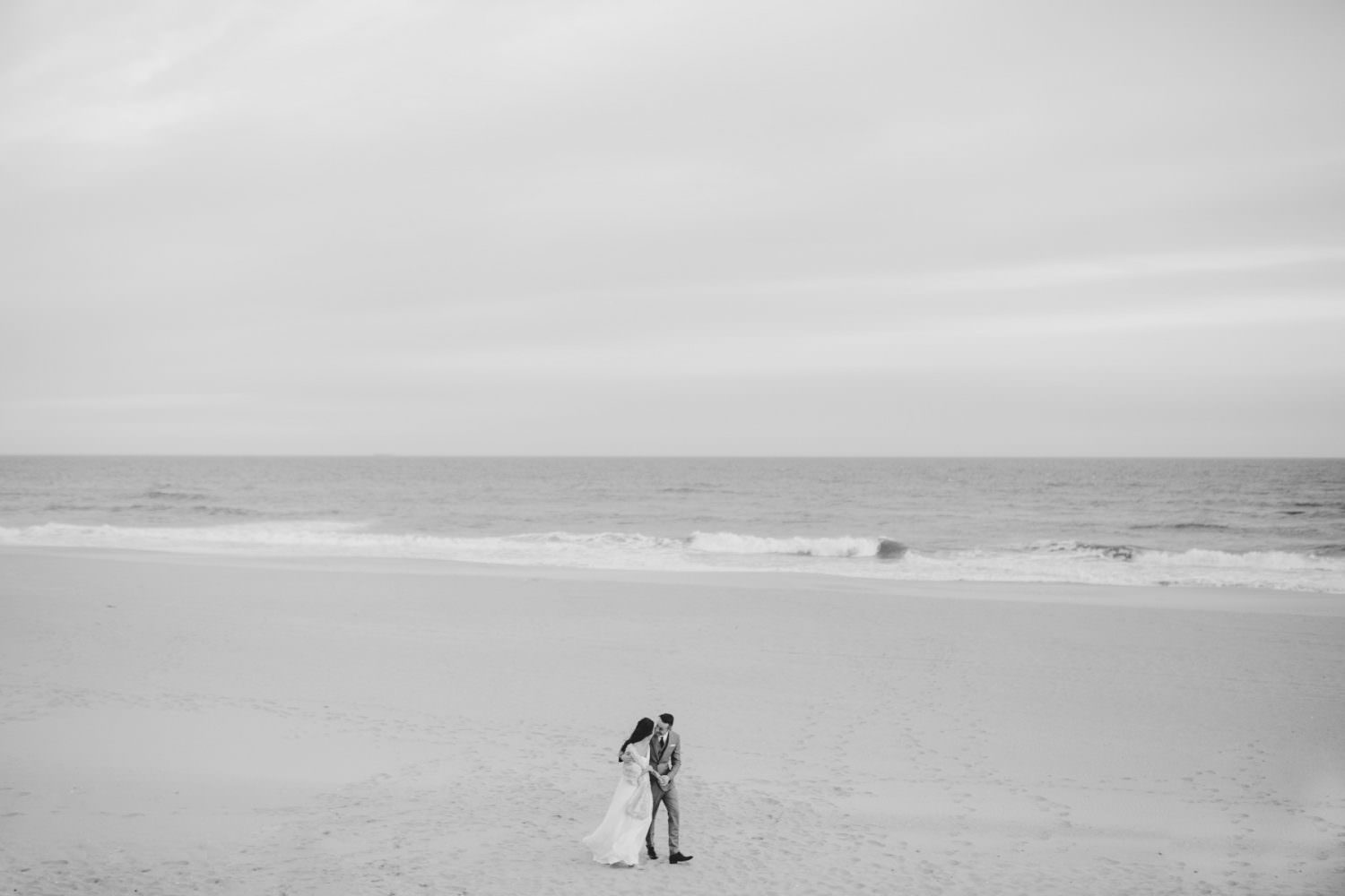 Black and white pulled back image of bride and groom walking on a Montauk Beach