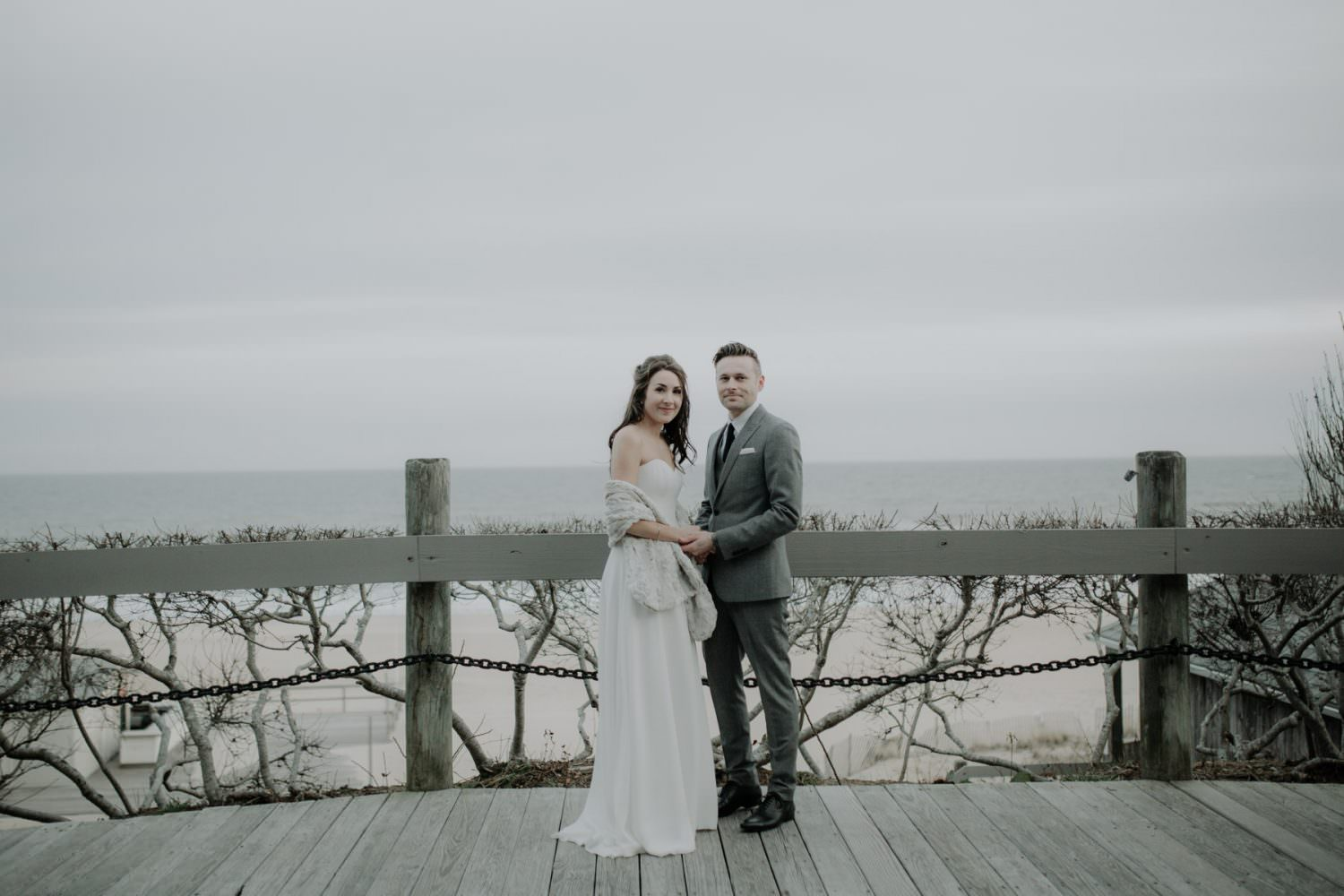 Bride and Groom posing looking at the camera with a beach setting