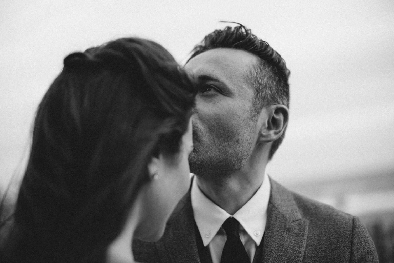 Groom kissing his bride on the forehead after their ceremony