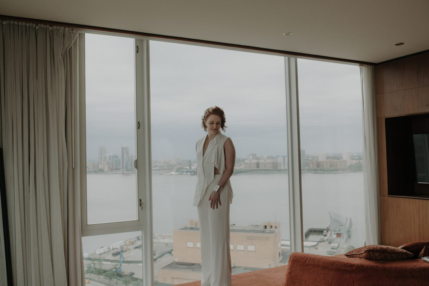 Portrait of bride by the window of the Standard hotel in New York with the hudson river in the background