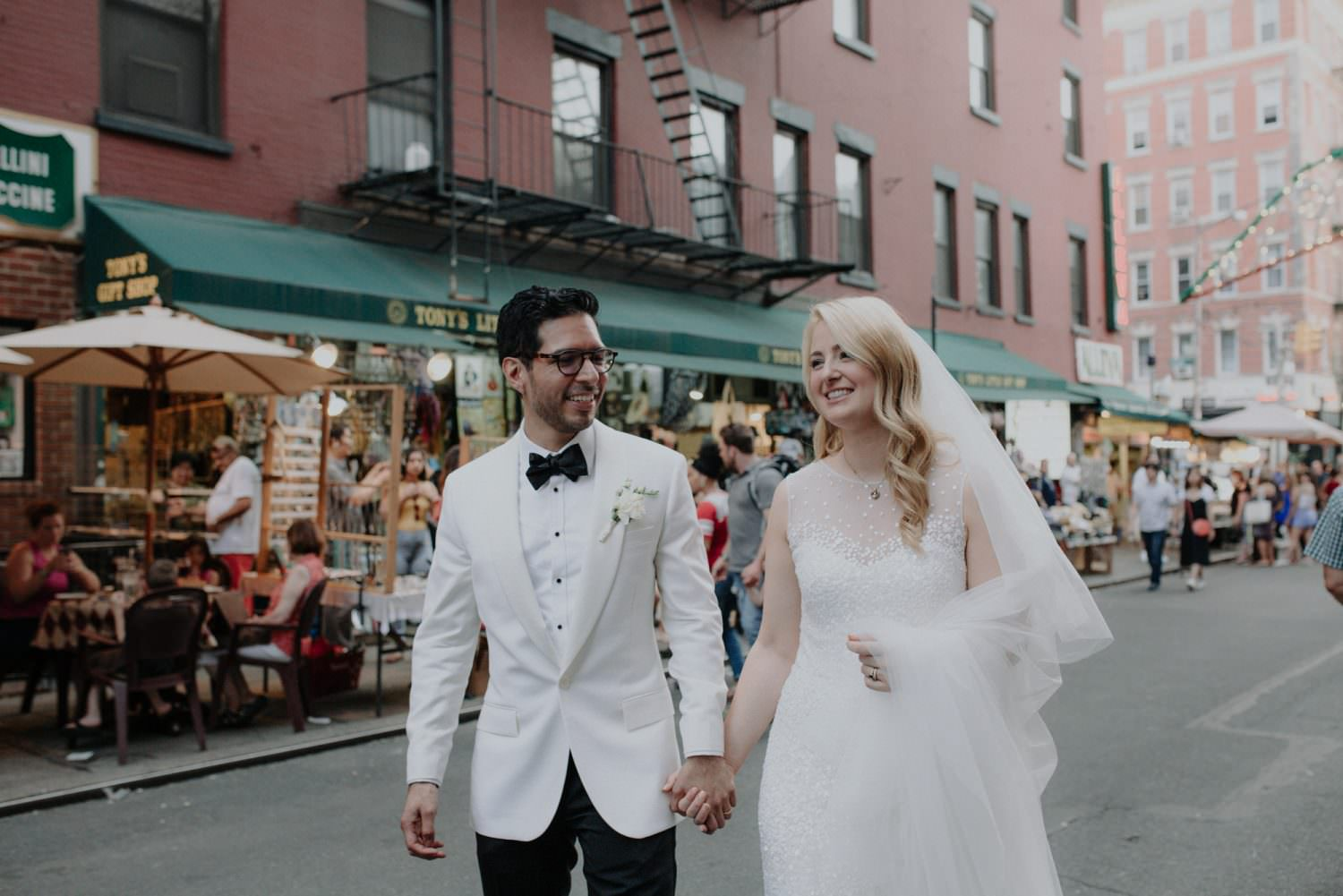 bride and groom holding hands while walking in Little Italy New York