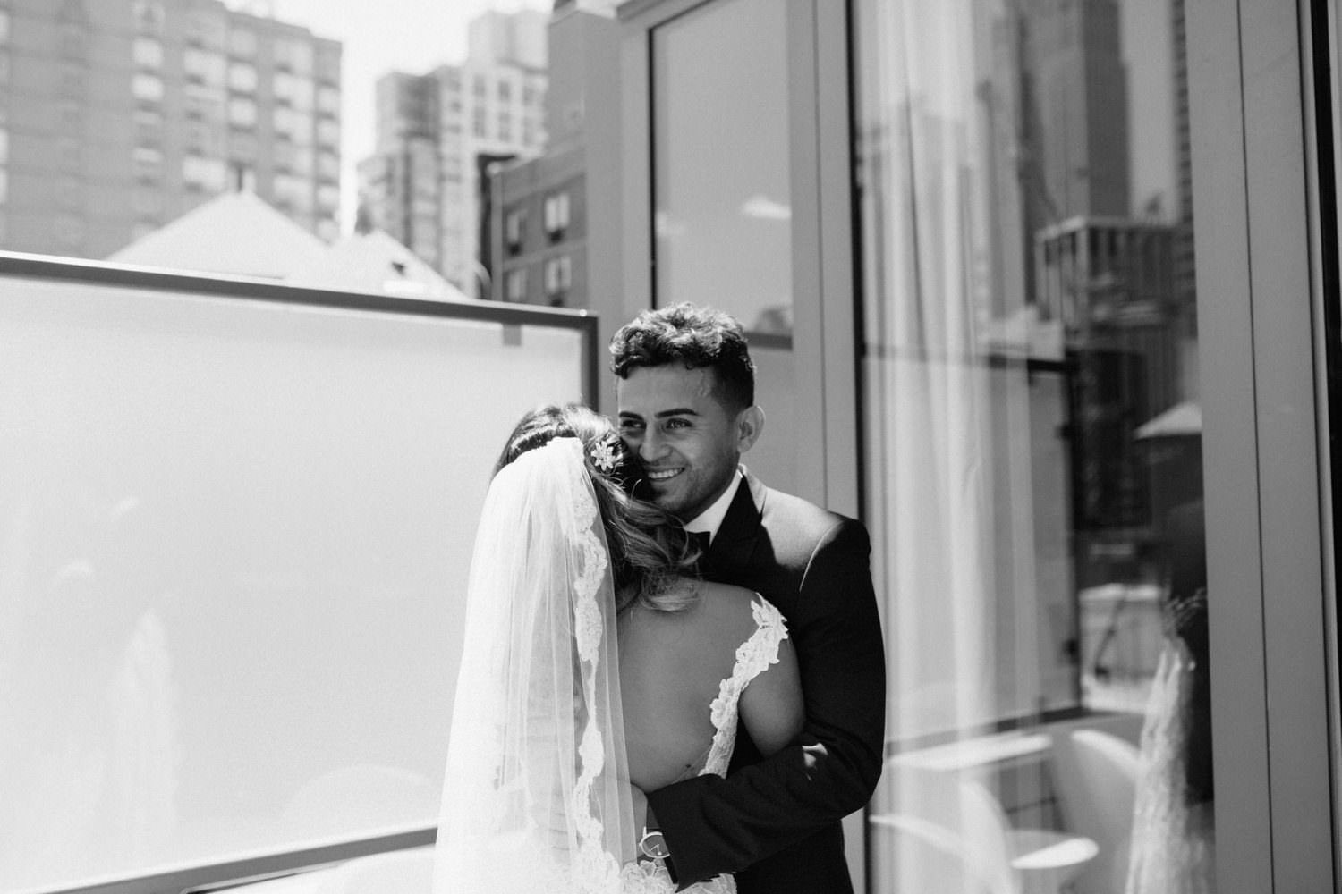 black and white image of groom emotional after seeing his bride