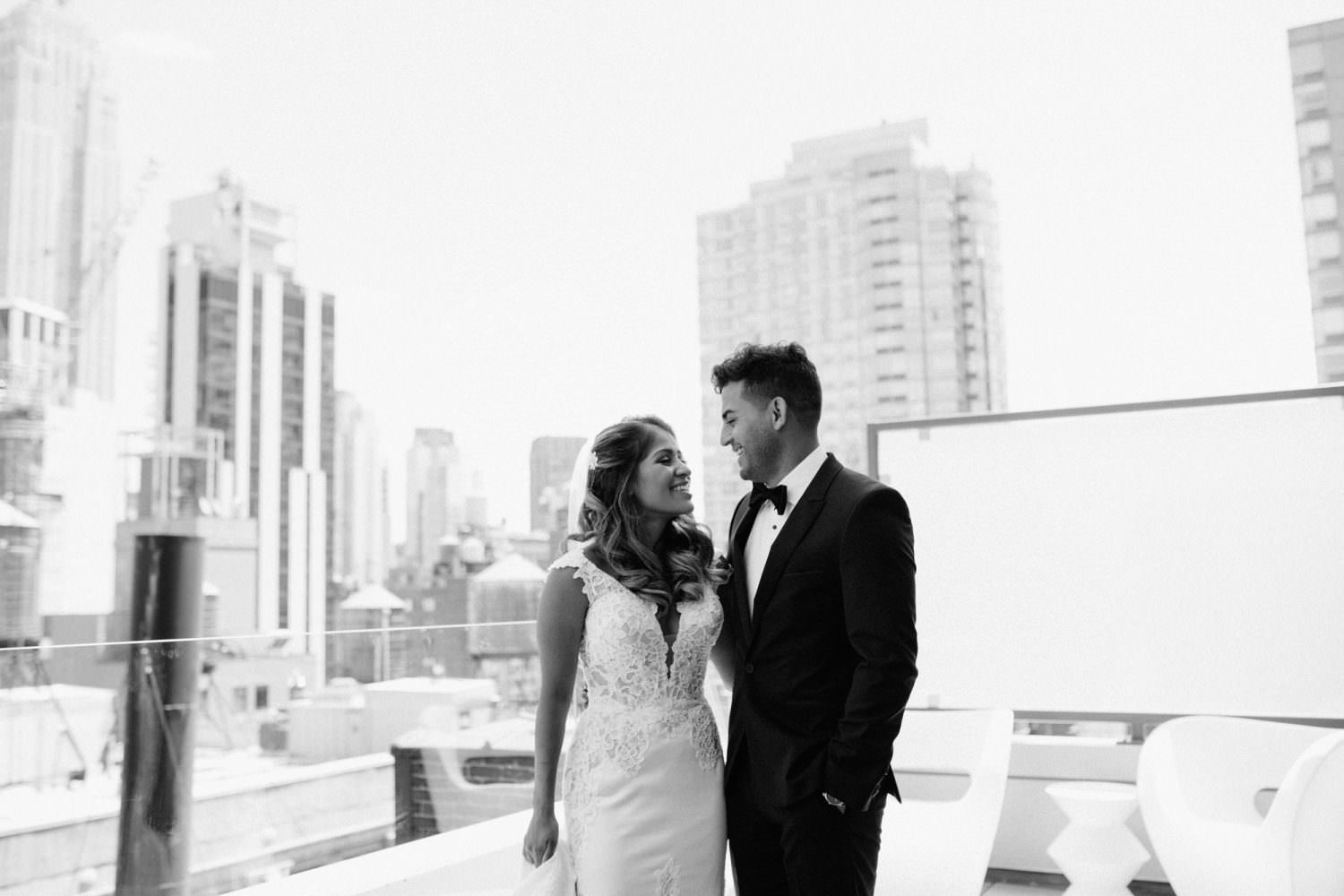 Black and white image of bride and groom on a hotel terrace in new york city