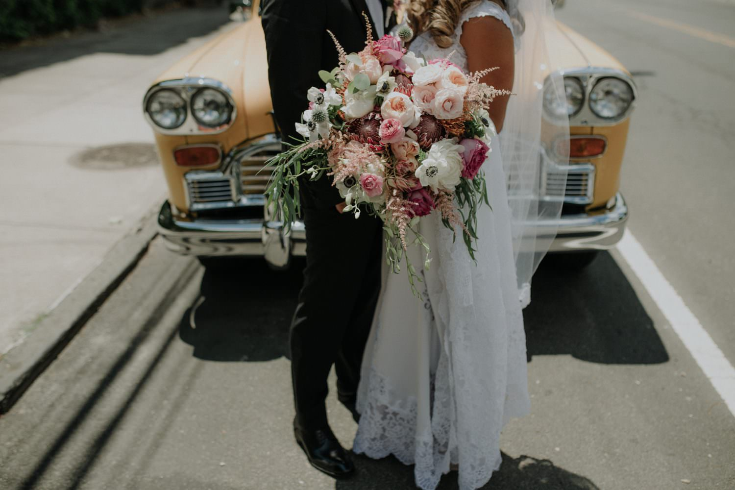 Bride and Groom standing close to each other holding the brides bouquet designed by Ivie Joy Flowers