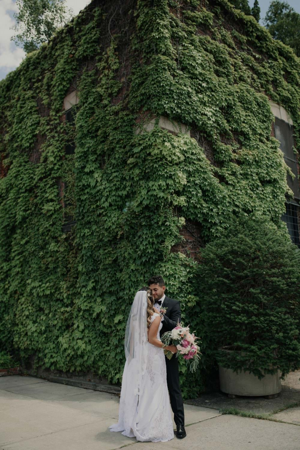Bride and Groom standing in front of the Ivy covered building, The Foundry