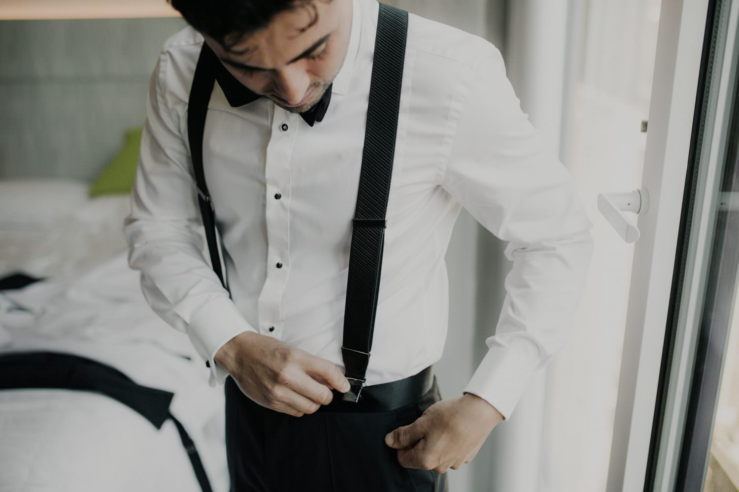 Groom adjusting his suspenders while getting ready on his wedding day