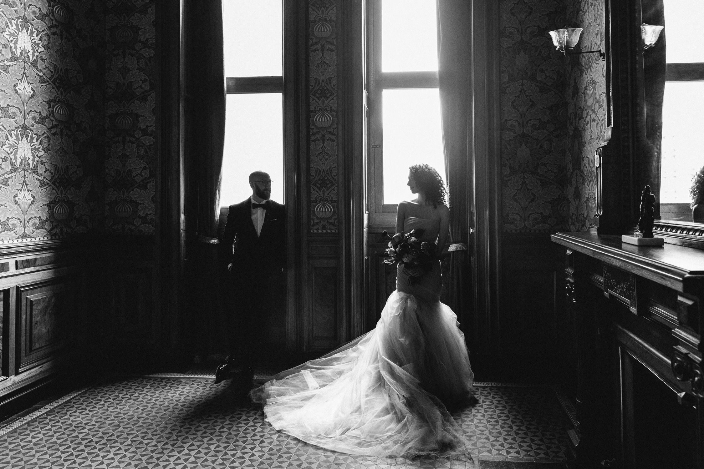 Bride and Groom stand in front of the windows at the Weylin in Brooklyn, NY