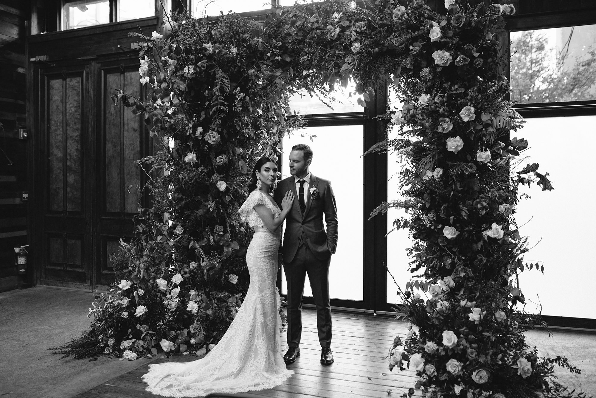 Black and white image of bride and groom posing in front of floral arch at brooklyn winery