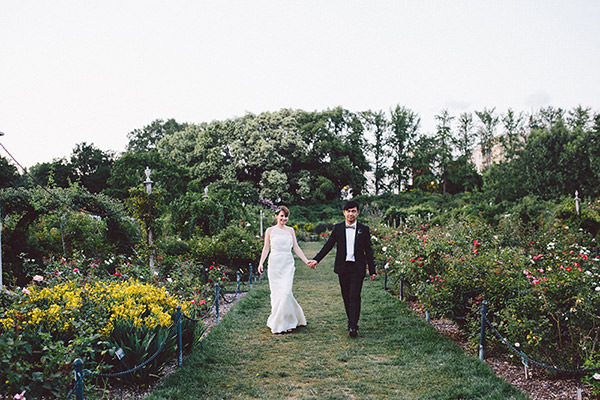 Bride and Groom holding hands amongst the rose garden at the Brooklyn Botanic Gardens
