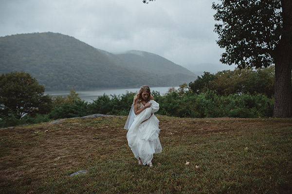 Bride walking in the Hudson Valley holding her dress