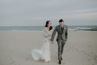 Bride and Groom holding hands walking on a beach in Montauk, NY