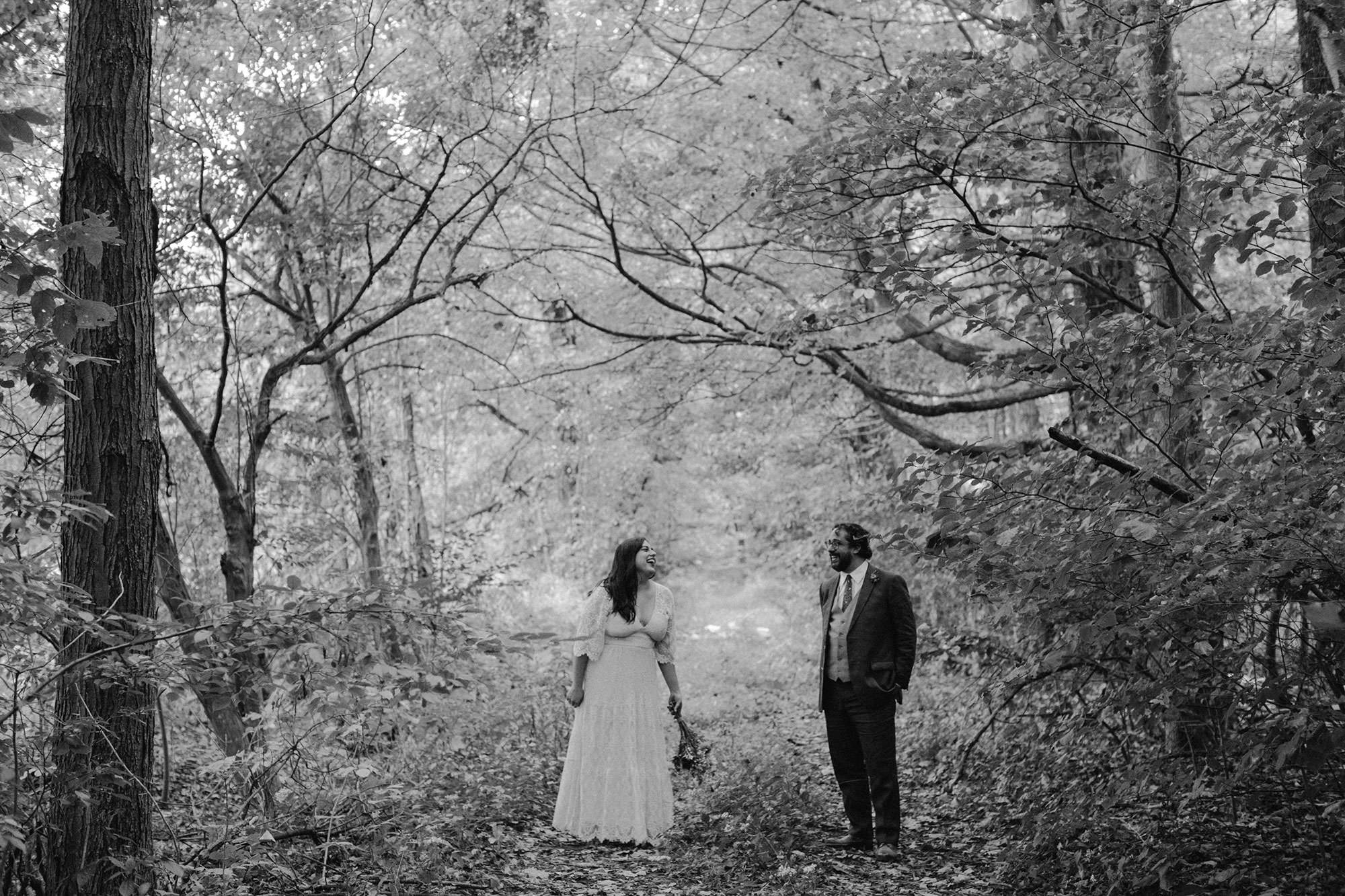 Bride and Groom laughing in the woods at their upstate new york wedding in Phoenicia