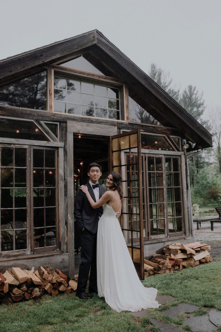 Bride and Groom pose in front of Glass House at Foxfire Mountain House