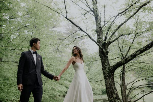 bride and groom walking and holding hands under a tree at Foxfire Mountain House