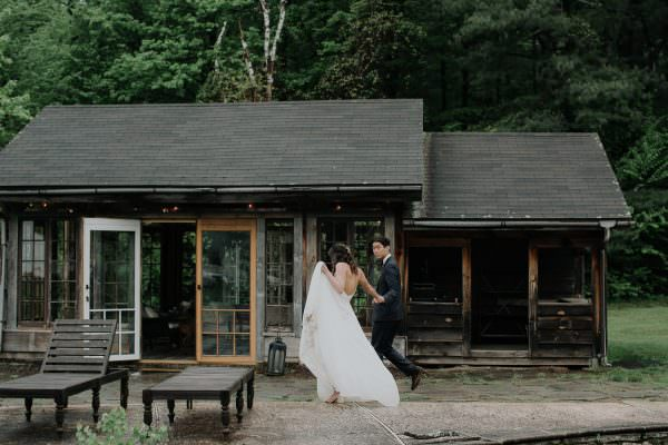 Bride and Groom run holding hands during their Foxfire Mountain House Wedding