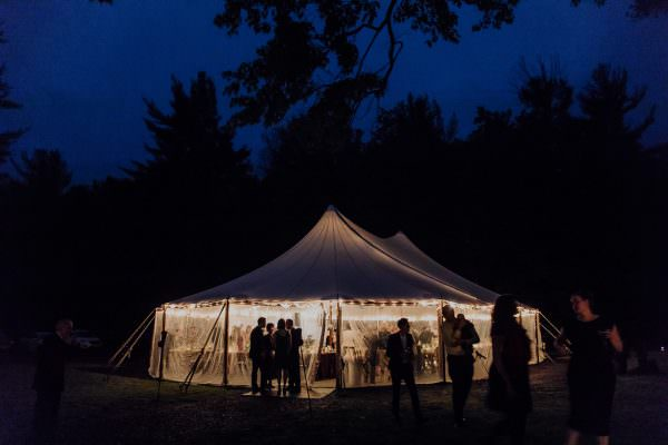 A night shot of the tent illuminated by reception lights under the night sky