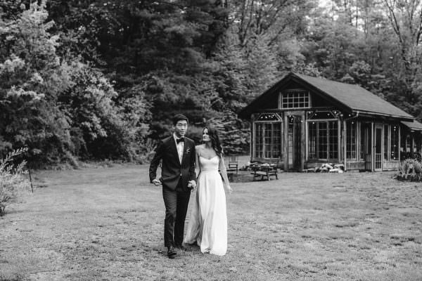 Bride and Groom walking with the glass house in the background of their Foxfire Mountain House Wedding