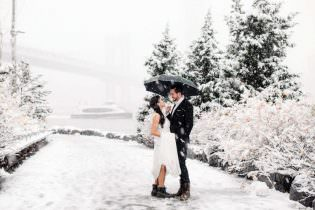 Bride and Groom pose on their snowy winter wedding day