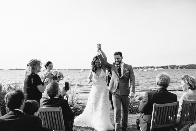 black and white image of bride and groom raising their arms with excitement after they married at the Crow's Nest