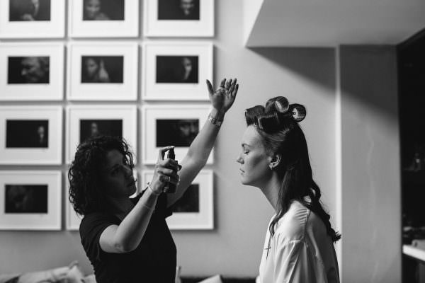 Black and white image of a bride getting her makeup done by Alexa Gould in NYC