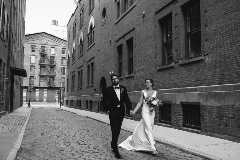 Bride and groom walk down a cobble stone street in Tribeca New York City on their wedding day