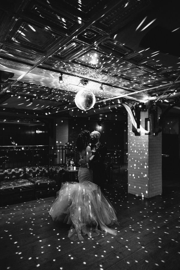 Black and White Image of Bride and Groom kissing under a disco ball at the Weylin Brooklyn