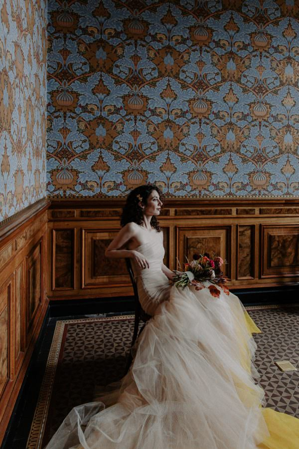 Bride sits casually in a room with patterned wallpaper surrounding her