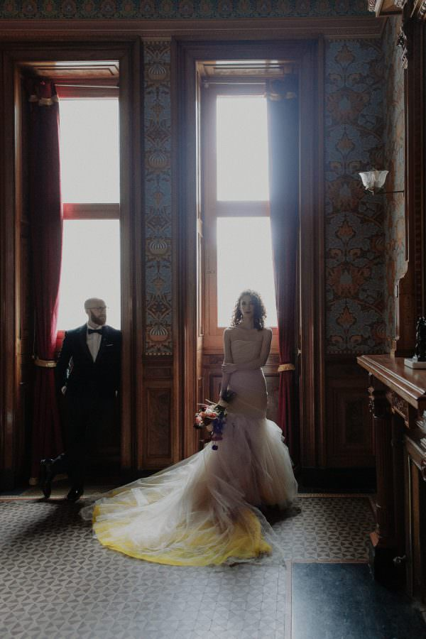Bride and Groom stand with the window light behind them in one of the wallpaper rooms inside the Weylin