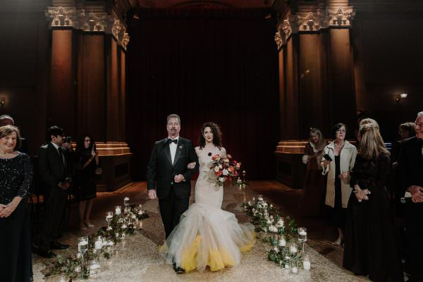 Bride holds her fathers arm while she walks down the aisle inn her yellow Vera Wang dress