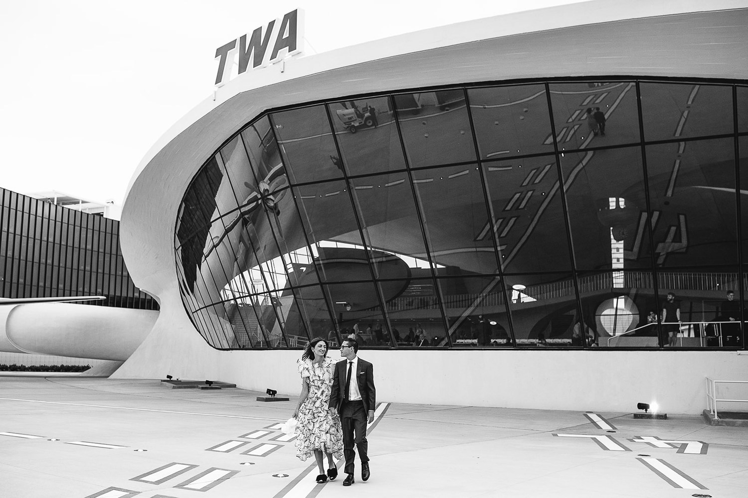 BRIDE AND GROOM WALK INN FRONT OF THE ICONIC TWA HOTEL TERMINAL